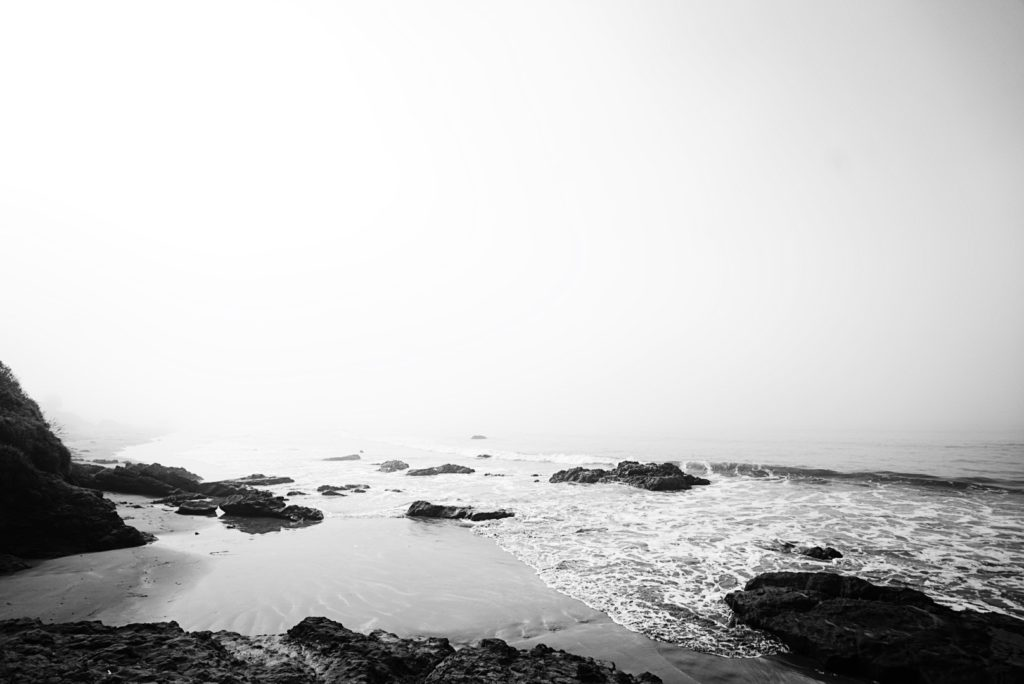 black and white photo of beach with rocks and ocean covered by fog