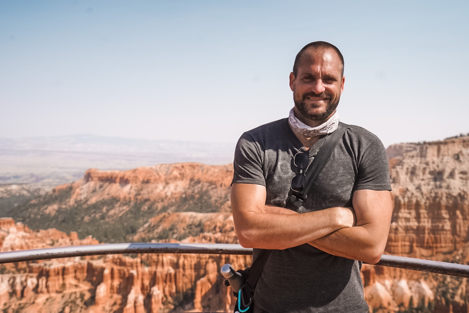 Male standing with arms crossed with Bryce Canyon in background