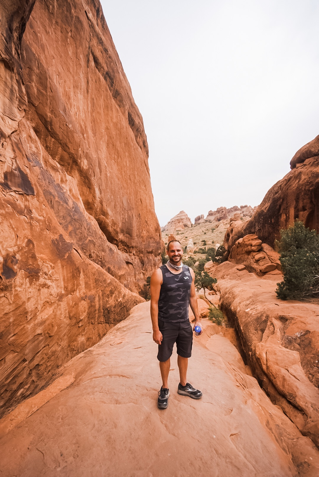 male standing on redrock in Arches national park
