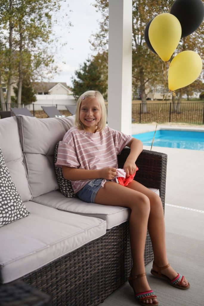young girl sitting on outdoor couch smiling at camera