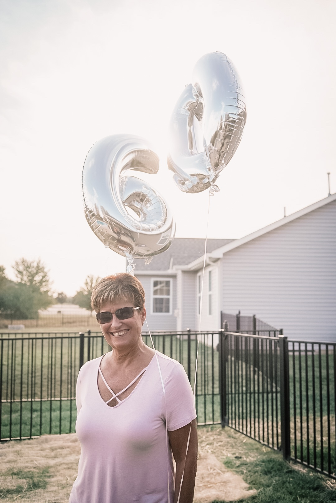 Woman standing smiling at camera holding two balloons - one balloon is a 6 and one balloon is a 0