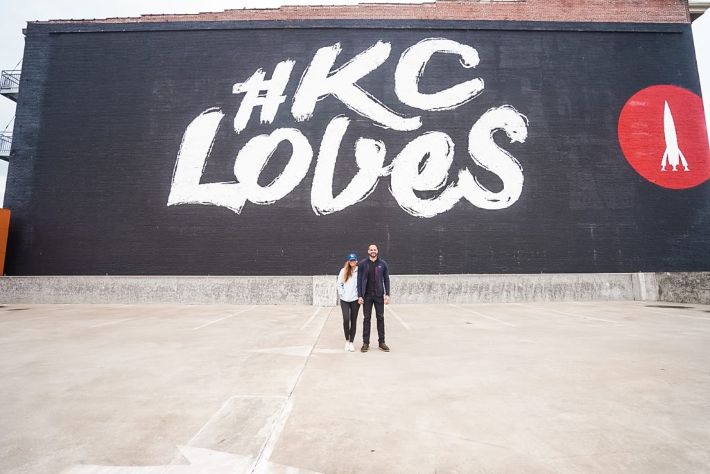 couple standing in front of a mural that says #KC Loves