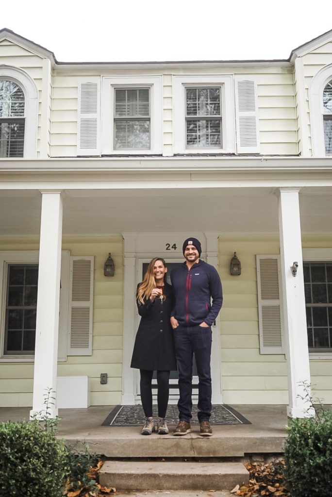 Woman in black coat standing next to man in coat and hat in front of yellow house. Woman is holding keys in front of her.