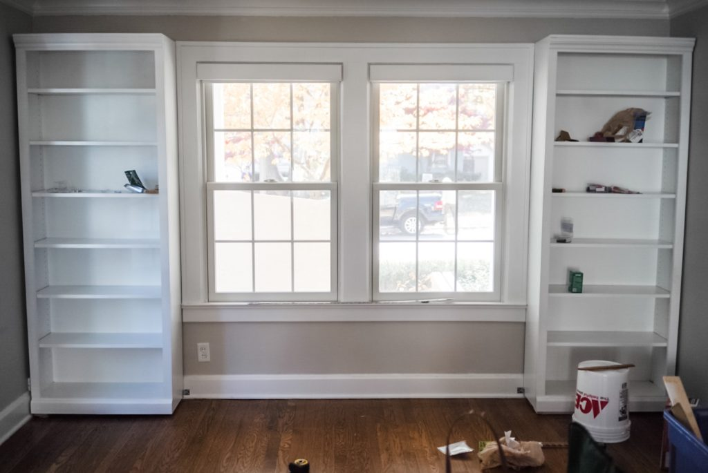 Two white empty bookshelves flanking a large window.