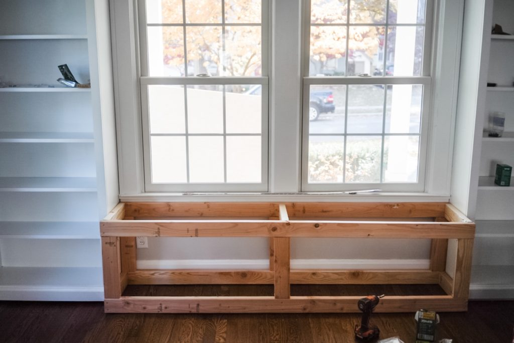 A frame of bench set between two white empty bookshelves under a window