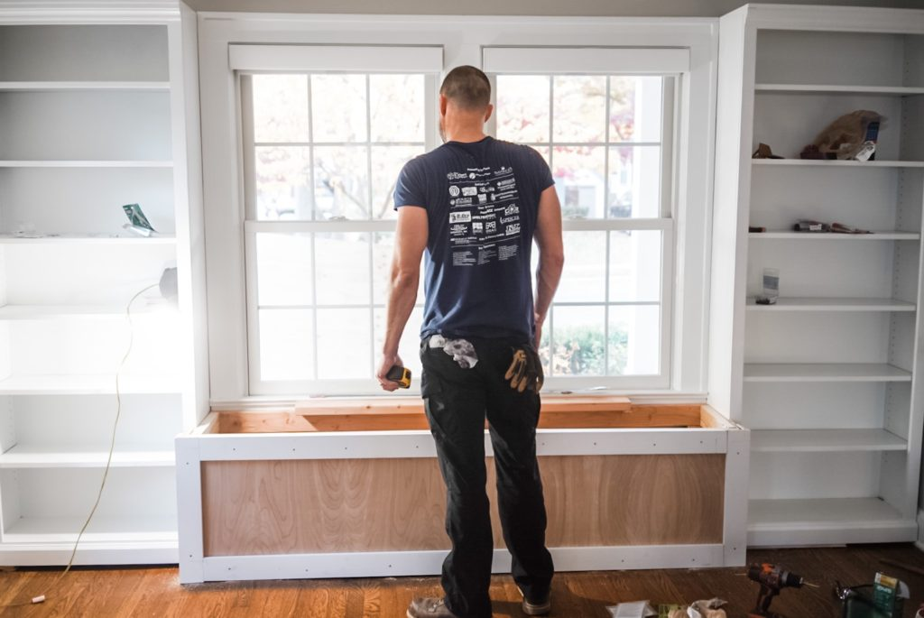 A man looking at a partially finished bench under a window between two empty bookshelves