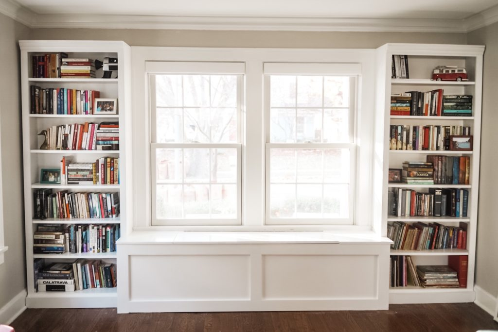Completed bench under window between two bookshelves now filled with books.
