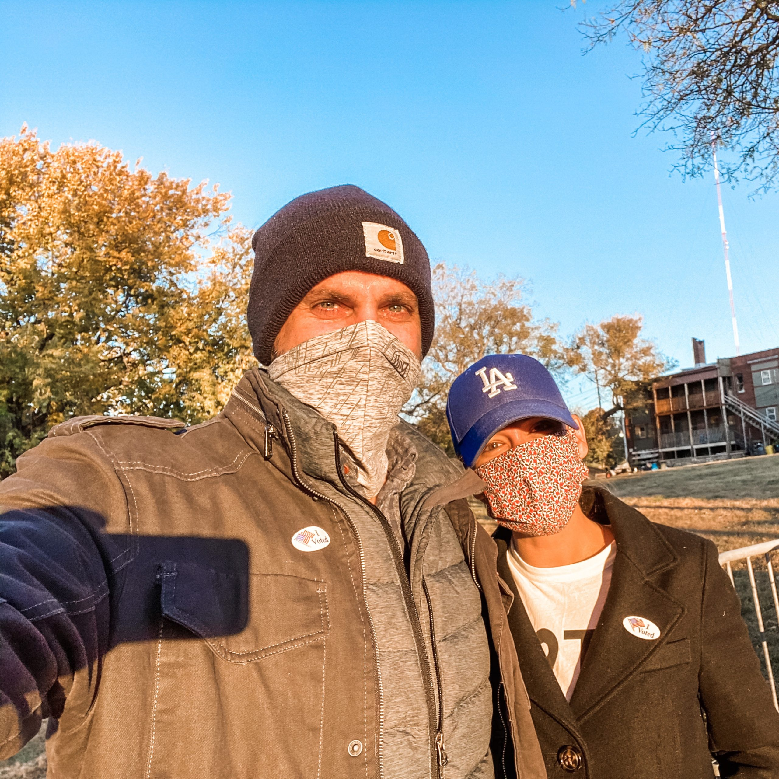 Man and woman both wearing masks with I voted stickers on.