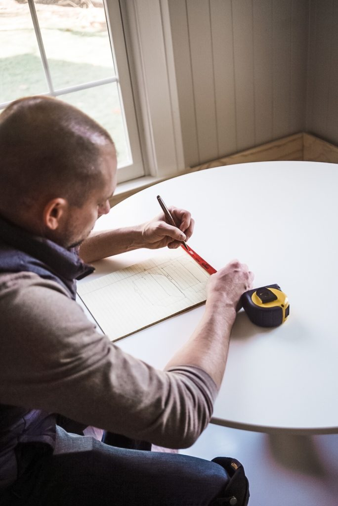 man drawing on pad of paper with measuring tape on table