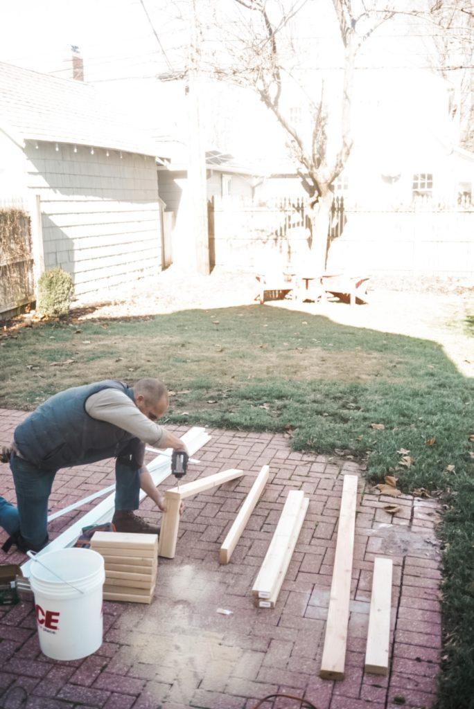 man cutting wood on brick patio