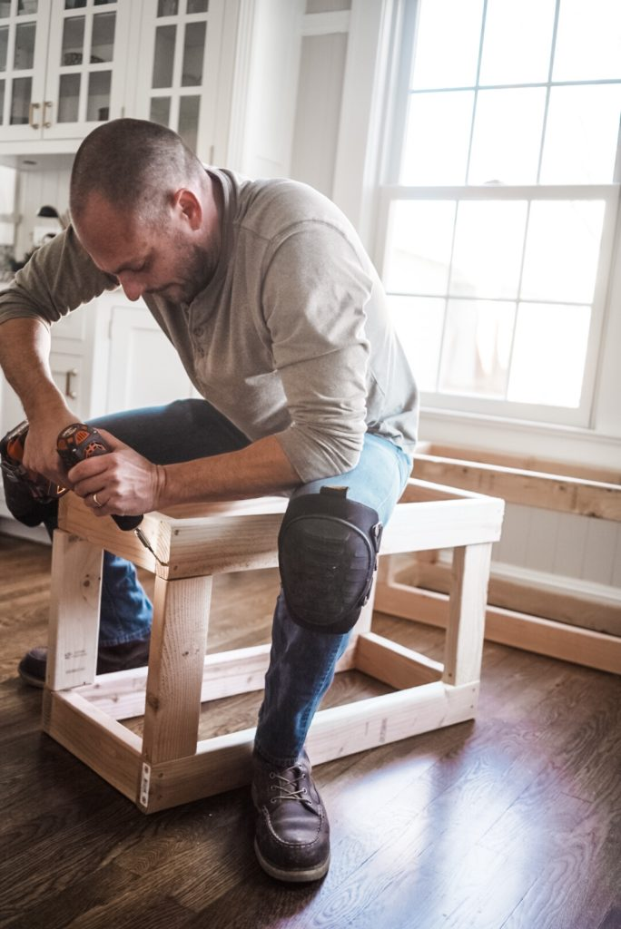 man drilling 2x4 wood together