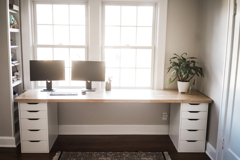 Desk with two computer screens and plant