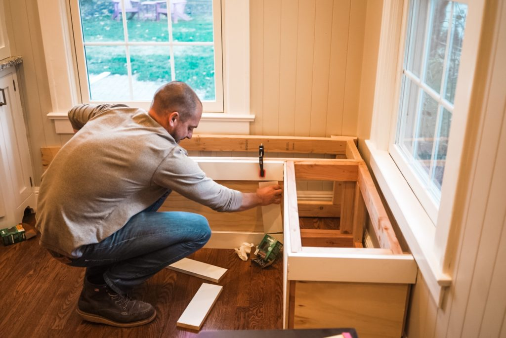 man placing trim on built in bench