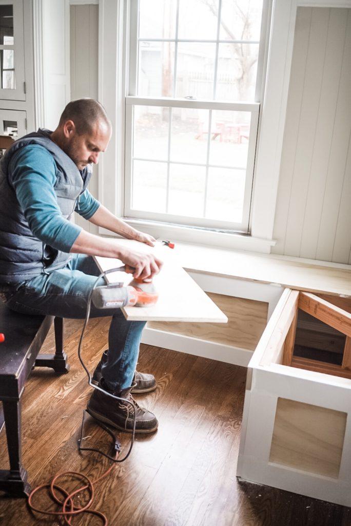 man sanding lids of a built in bench