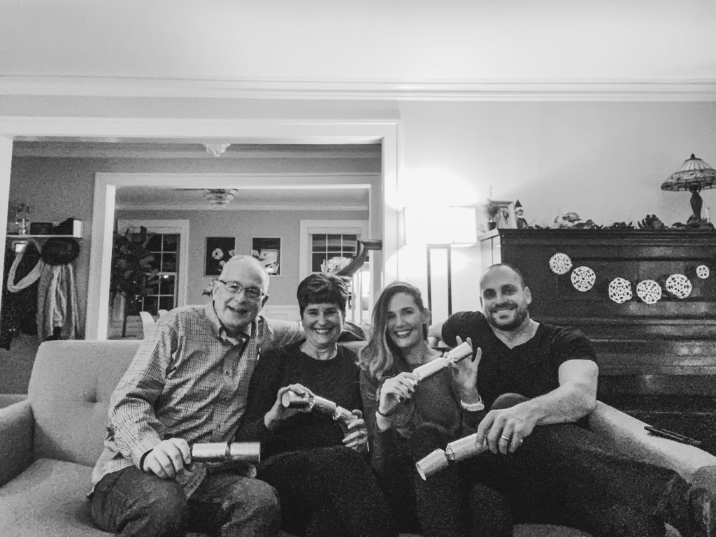 Four people sitting on couch with poppers