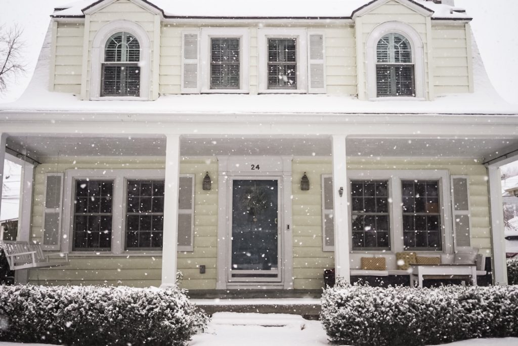 Yellow house with blue front door and with snow falling