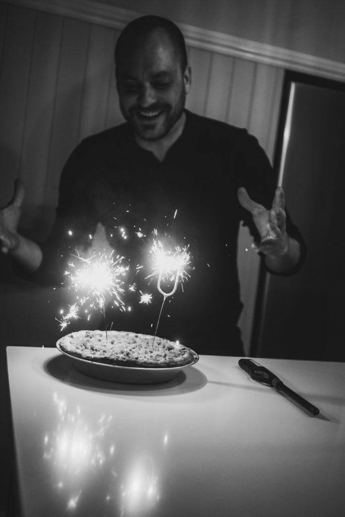 White man smiling at two sparkling candles a 4 and 0 on an apple pie on a kitchen counter