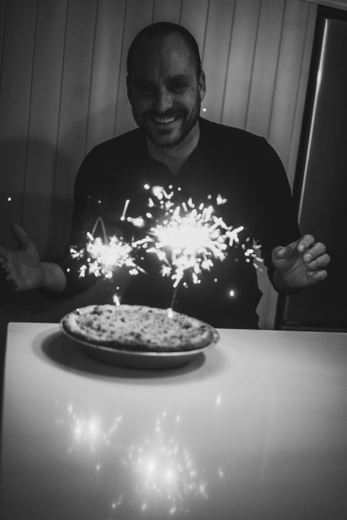 White male smiling at camera with two sparklers burn on an apple pie