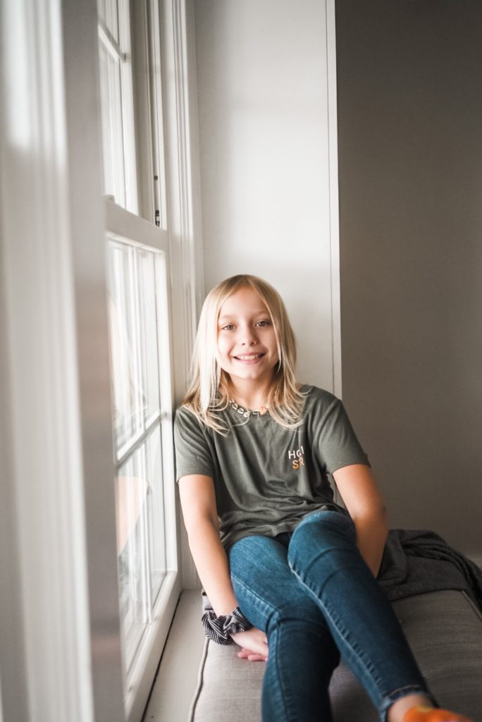 Young girl age 10 sitting on bench smiling at camera