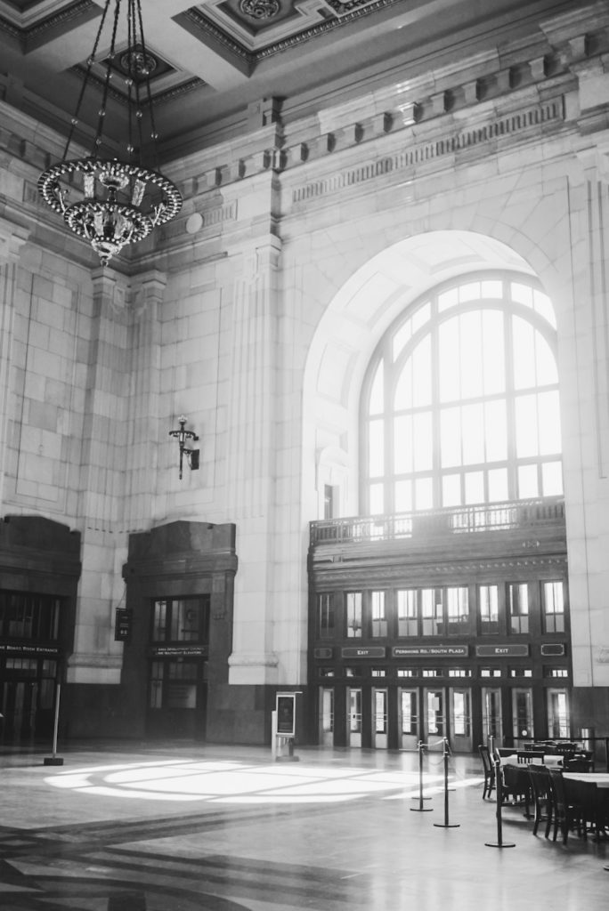 Black and white photo of a train station with large arched window