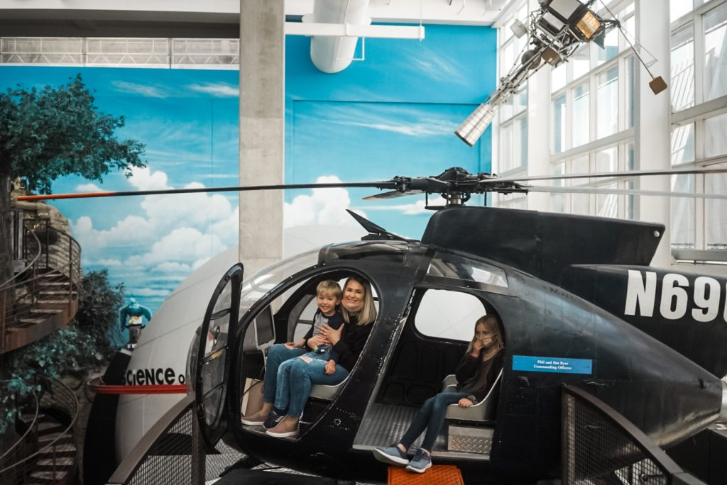 Young boy and mother sitting in a helicopter. Young girl in second row of helicopter seats.