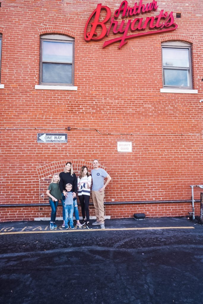 Family of five standing in front of a building that reads Arthur Bryant's. From left to right young girl, woman, young boy, teenage girl, and man