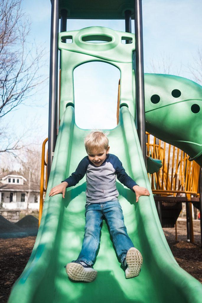 Young boy sliding down a green slide