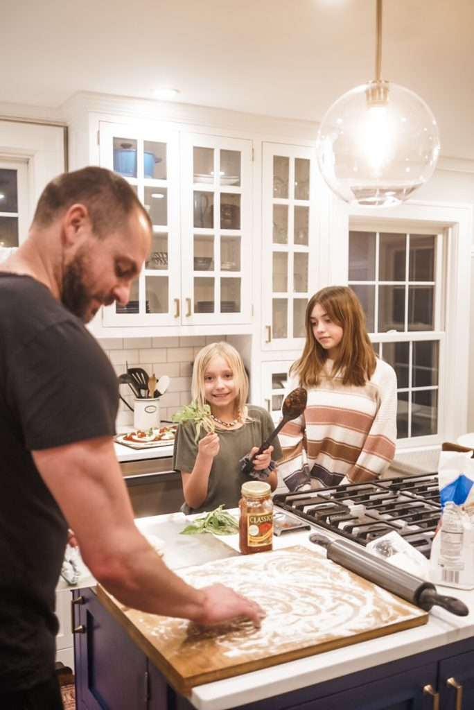 Man in foreground rolling pizza dough. Young girl holding basil and spoon with marinara; teenage girl looking down at younger girl