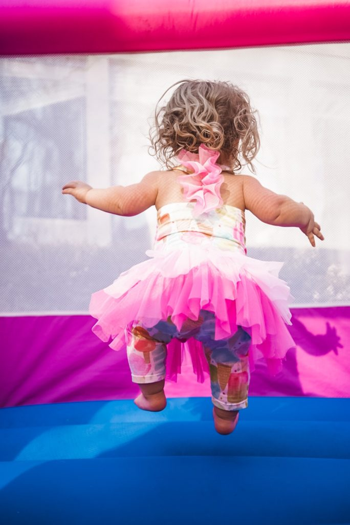View of back of a young girl in mid air jumping  in a bounce house. She is wearing a tutu