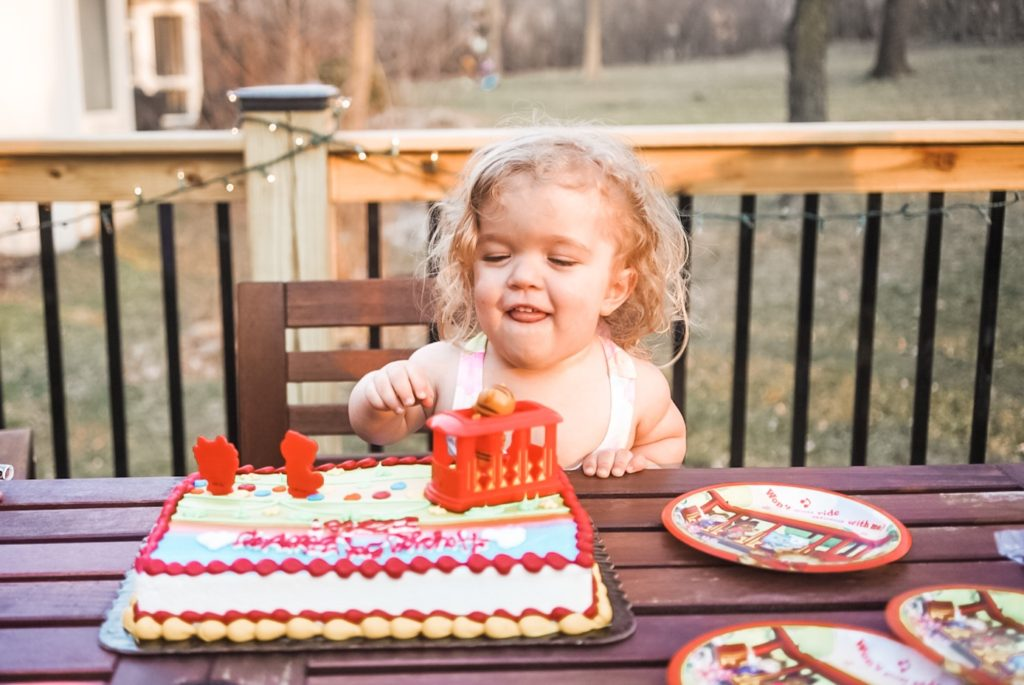 Young girl sitting behind a birthday cake and smiling.