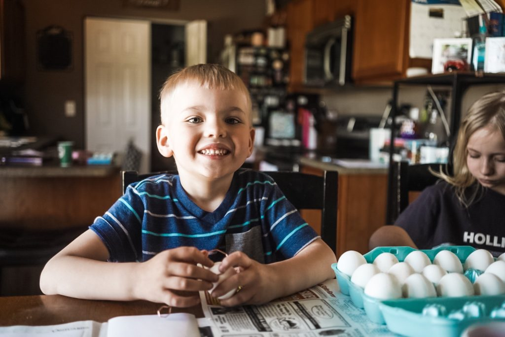 Young boy smiling at camera with eggs in his hand