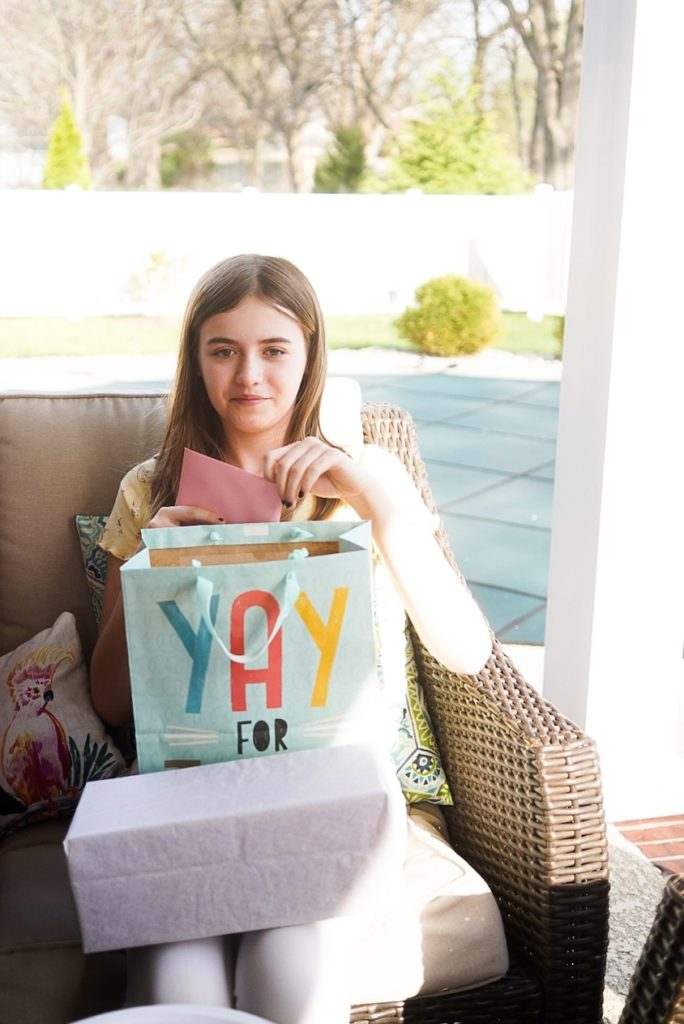 Young girl looking at camera with a bag in her lap that reads YAY