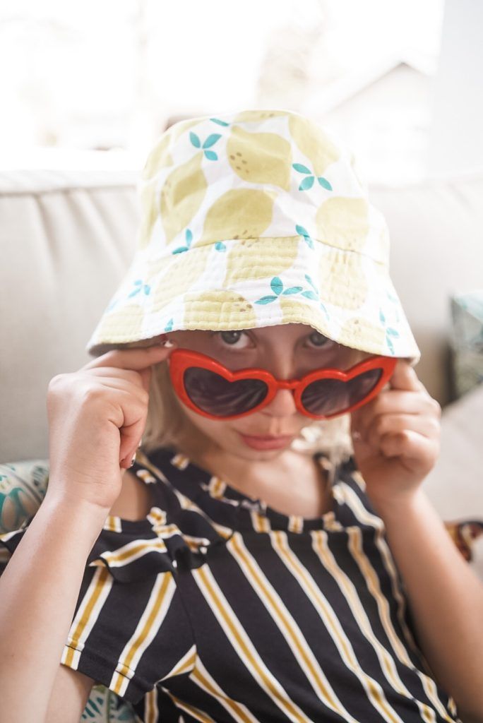young girl wearing heart sunglasses and hat with lemons on it