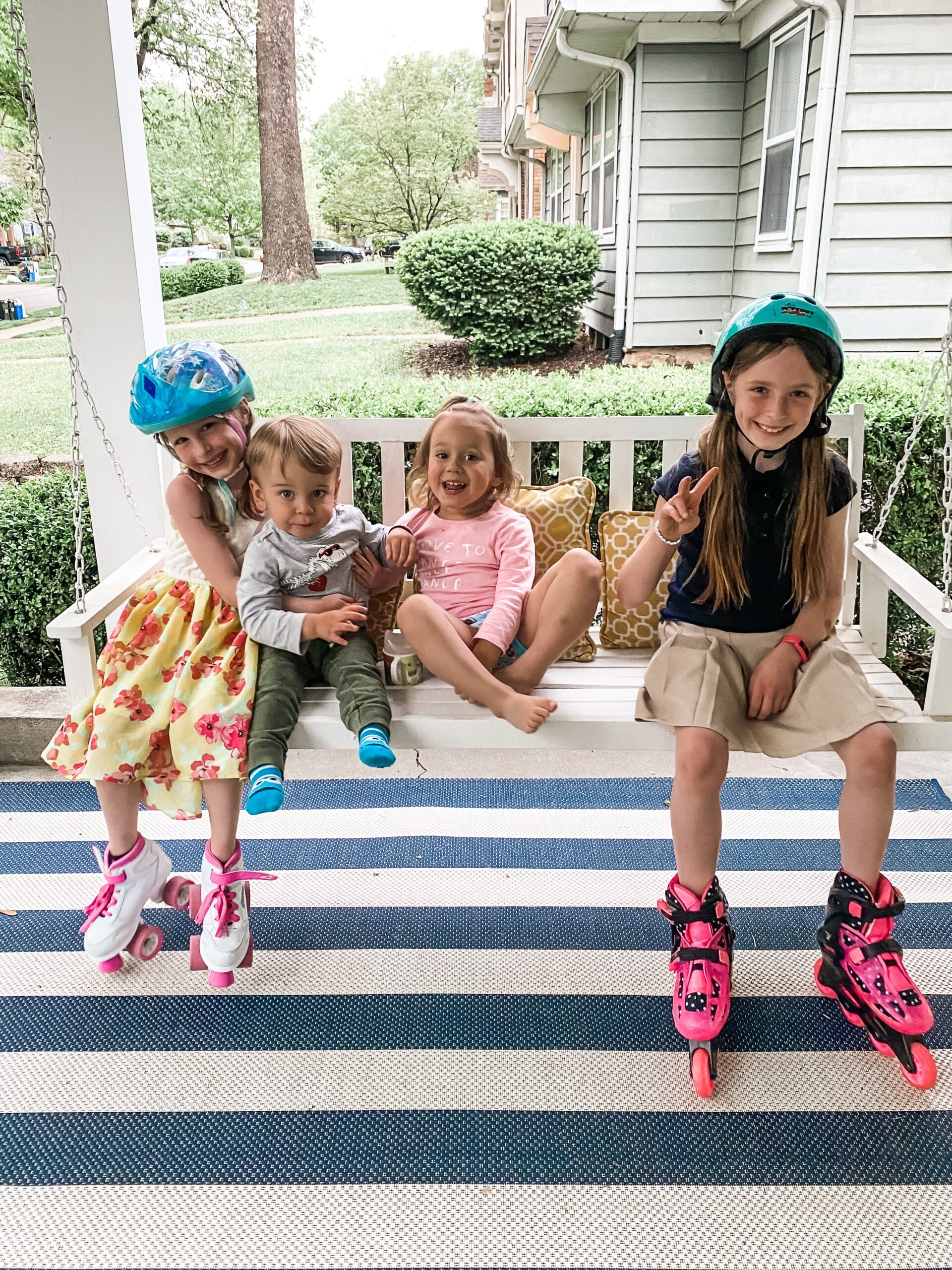 Four children on porch swing. Two girls are wearing bike helmets and roller blades. Younger girl and younger boy are sitting between the two girls in roller blades.