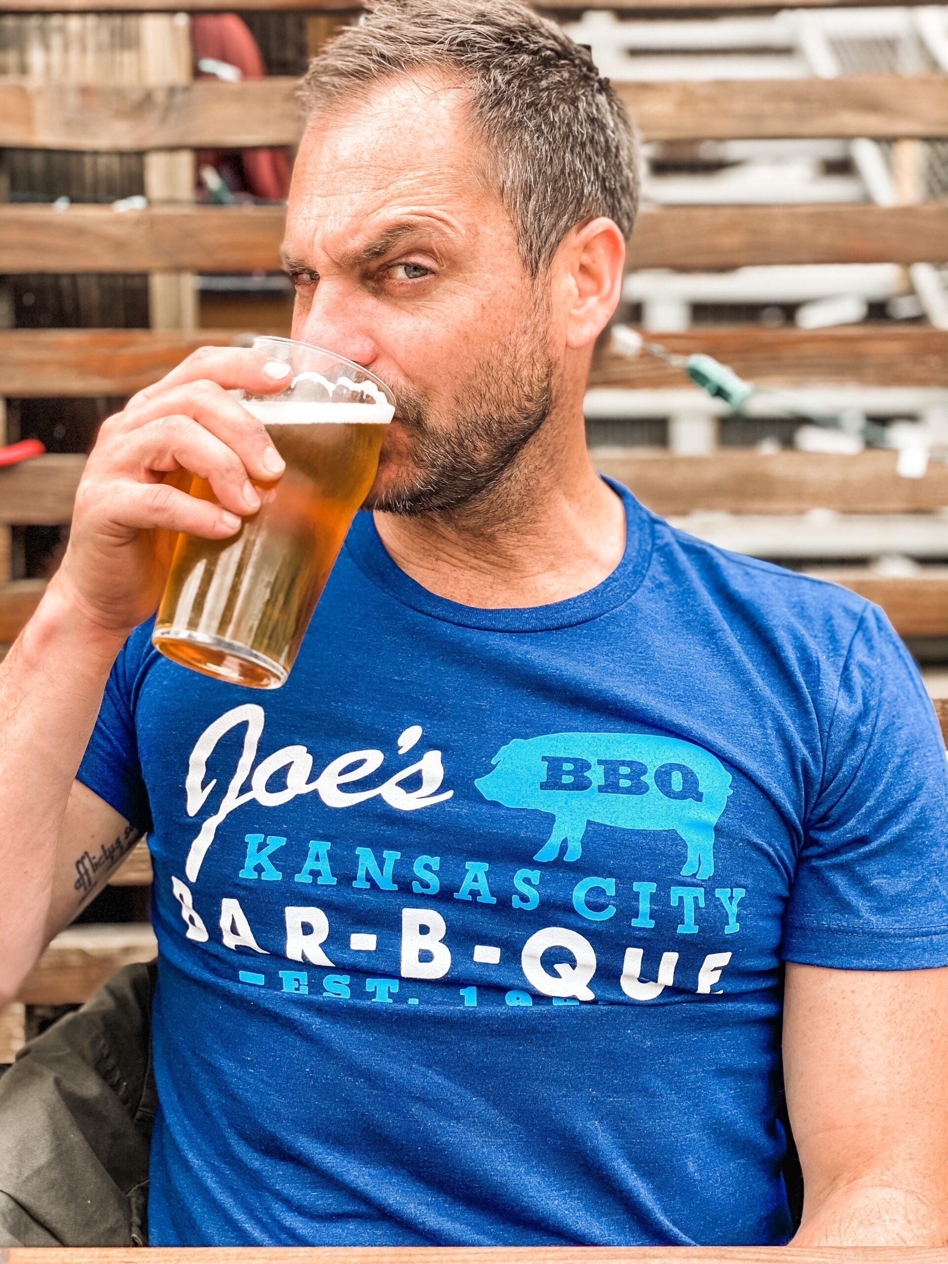 White man with beard drinking beer wearing blue t-shirt that reads Joe's bbq Kansas City Bar-B-Que