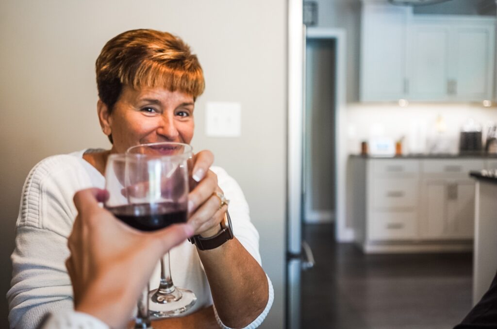 My mom wearing a white shirt toasting a glass of wine