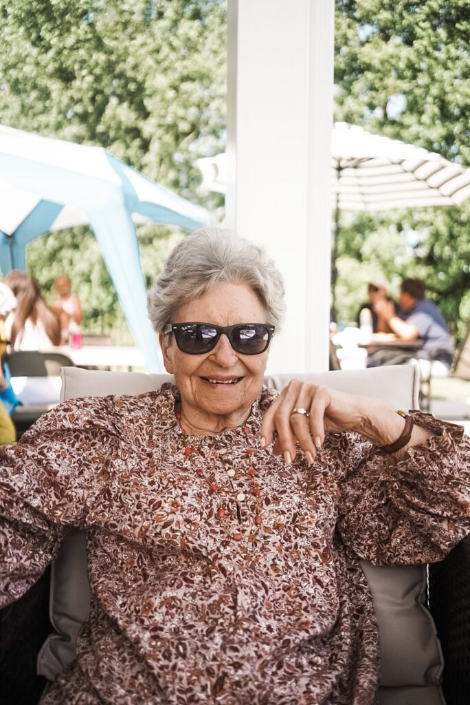 older woman wearing ray ban sunglasses smiling at camera. She is wearing a flowered shirt.