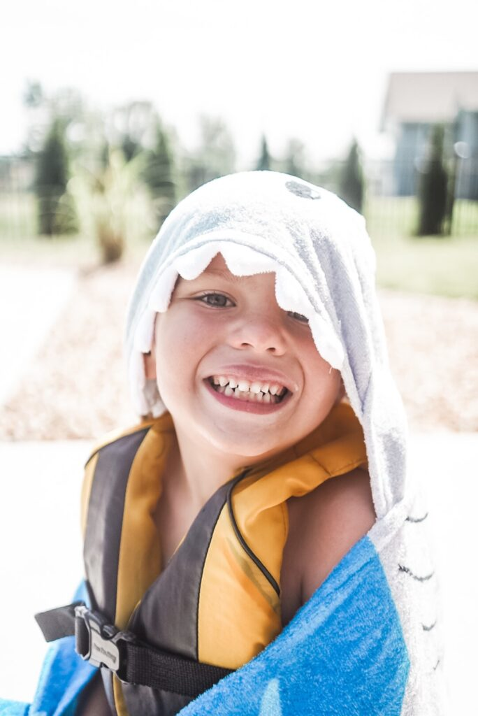 Young boy wearing a yellow life vest and towel over his head that looks like a shark