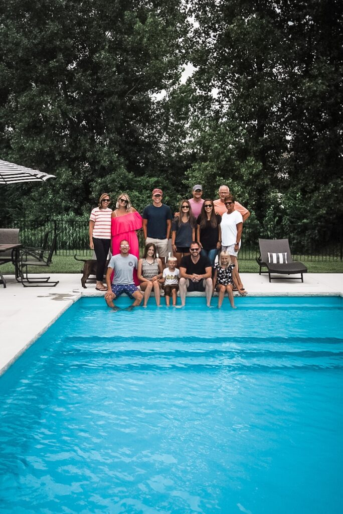 Group photo of 13 people standing in front of a pool