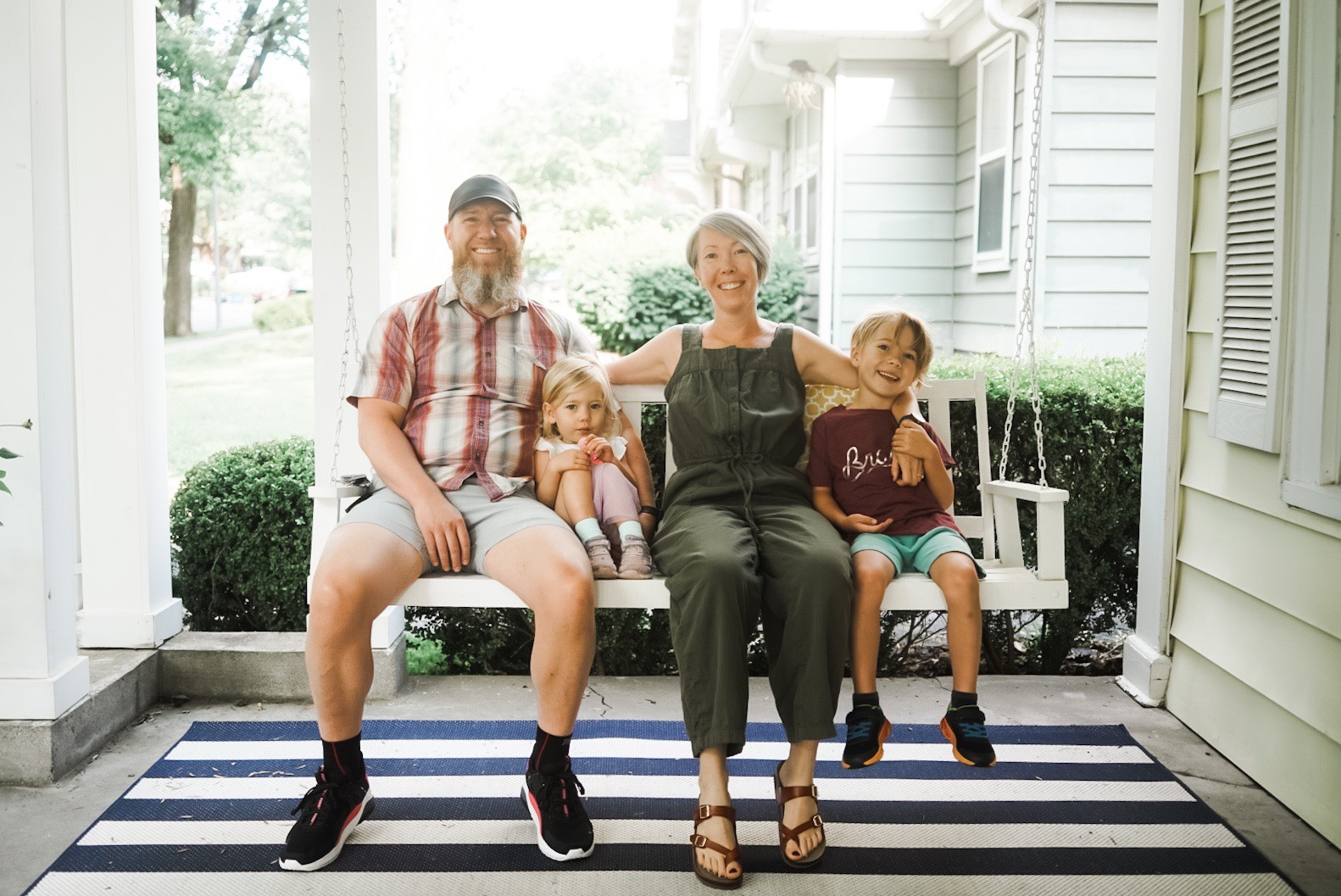 Two adults and two small children sitting on a porch swing
